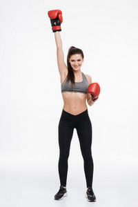 Full length portrait of a smiling successful sports woman wearing boxing gloves with one fist in the air isolated on a white background