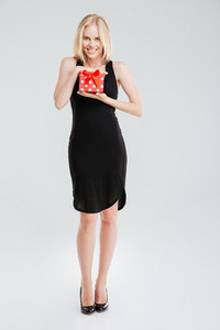 Full length portrait of a smiling woman in black dress holding gift isolated on a white background