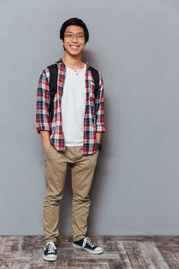 Full length portrait of a smiling young asian man with backpack standing holding hands in pockets isolated on the gray background