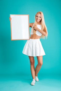 Full length portrait of a smiling young blonde woman standing and pointing finger at blank board isolated on the blue background