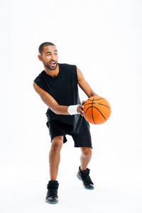 Full length portrait of a smiling young sports man playing basketball isolated on a gray background