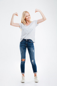 Full length portrait of a smiling young woman showing her muscles isolated on a white background