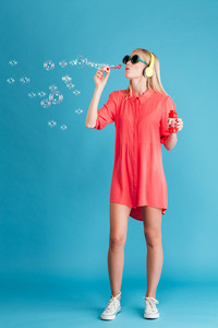 Full length portrait of a stylish blonde woman in sunglasses blowing soap bubbles and listening music with headphones over blue background