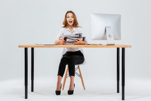 Full length portrait of a surprised happy young businesswoman sitting at the table with pc over white background