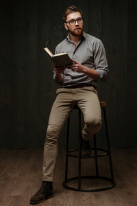 Full length portrait of a thoughtful young man in eyeglasses sitting on chair and reading book isolated on a black wooden background