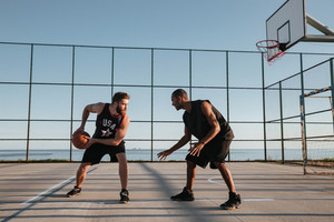Full length portrait of a two basketball players having game at the playground