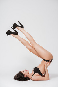 Full length portrait of a young attractive woman wearing sexy lingerie and laying with her legs raised isolated on the white background