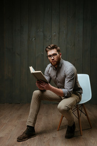 Full length portrait of a young bearded man in eyeglasses holding book while sitting on chair and looking at camera isolated on a black wooden background