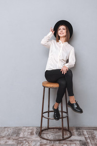 Full length portrait of a young beautiful cheerful girl in hat sitting on chair isolated on the gray background