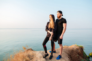 Full length portrait of a young beautiful fitness couple standing on a hill and looking at something