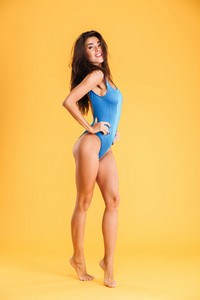 Full length portrait of a young beautiful woman in swimsuit posing isolated on the orange background