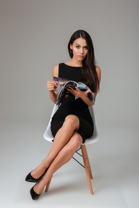Full length portrait of a young brunette woman sitting on the chair and holding magazine over gray background