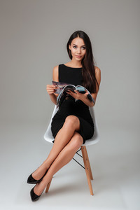 Full length portrait of a young brunette woman sitting on the chair and reading magazine over gray background