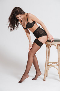 Full length portrait of a young brunette woman wearing lingerie with stockings and posing on a chair isolated on a white background