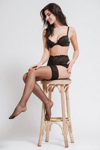 Full length portrait of a young brunette woman wearing lingerie with stockings and sitting on a chair isolated on a white background