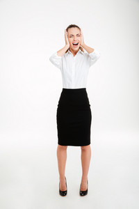 Full length portrait of a young businesswoman covering her ears and shouting over white background