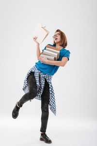Full length portrait of a young casual female student with heap of books isolated on a white background