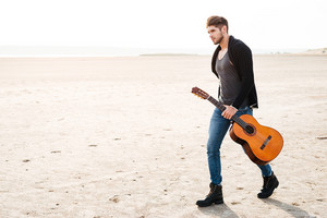 Full length portrait of a young casual man walking across seashore with guitar