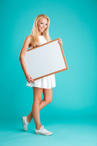 Full length portrait of a young cheerful woman walking and holding blank board isolated on the blue background