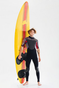 Full length portrait of a young happy surfer holding surf board isolated on the white background