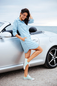 Full length portrait of a young happy woman standing near her car outdoors