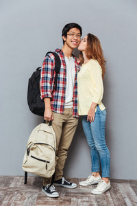 Full length portrait of a young interracial couple in love standing and kissing with backpacks isolated on the gray background