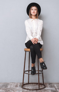 Full length portrait of a young serious woman in hat sitting on chair isolated on the gray background
