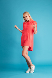 Full length portrait of a young smiling girl celebrating success isolated on a blue background
