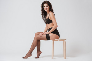 Full length portrait of a young smiling woman in lingerie posing on a chair isolated on a white background
