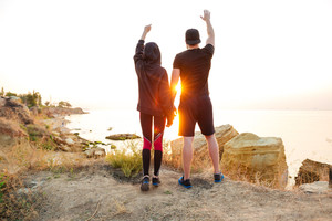 Full length portrait of a young sports couple standing on a hill and greeting sunset