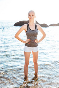 Full length portrait of a young woman standing with hands on hips in the water