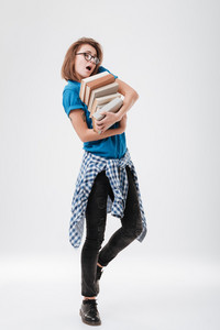 Full length portrait of an exhausted young girl in glasses holding heap of books isolated on a white background