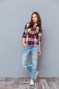Full length portrait of attractive young woman in jeans and plaid shirt standing over grey background