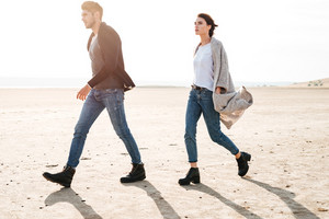 Full length portrait of casual young couple walking along seashore in sunlight
