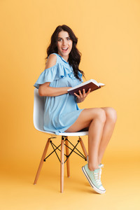 Full length portrait of excited young woman in blue dress holding book and sitting on the chair isolated on a orange background