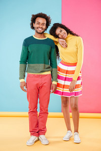 Full length portrait of happy tender young couple in bright clothes standing over colorful background
