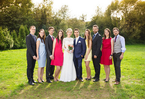 Full length portrait of newlywed couple posing with bridesmaids and groomsmen in green sunny park