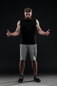 Full length portrait of trainer. show fingers up. isolated dark background