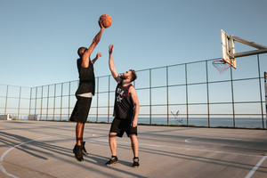 Full length portrait of two players with basketball at the playground