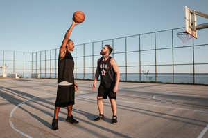 Full length portrait of two young men playing basketball at the playground
