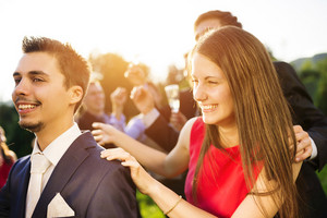 Full length portrait of wedding guests dancing and having fun at the wedding garden party in a green sunny park
