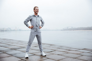 Full length Runner in gray sportswear standing with arms at hips near the water. Side view