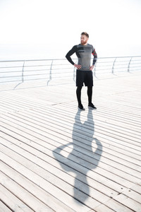 Full length runner near the sea. looking away. arms at hips