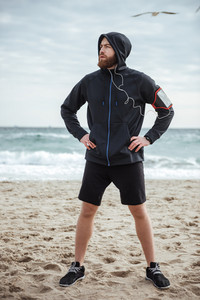 Full length runner on beach. front view. looking away