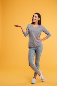 Full length showing model in studio. looking away. arm at hip. Holding invisible copyspace on the pound. isolated orange background