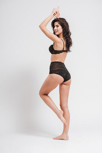 Full length side view portrait of a sexy brunette woman standing and posing with hands raised isolated on a white background