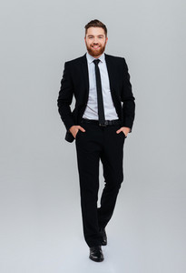 Full length smiling bearded business man in black suit with hands in pockets looking at camera. Front view. Isolated gray background