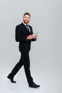 Full length smiling bearded business man in suit moves with tablet computer in studio and looking at camera. Isolated gray background