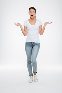 Full length surprised model in t-shirt and jeans. choosing between copyspace. isolated white background