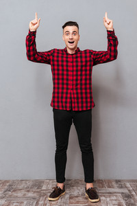 Full length surprised young man in shirt and black jeans pointing up and looking at camera. Isolated gray background